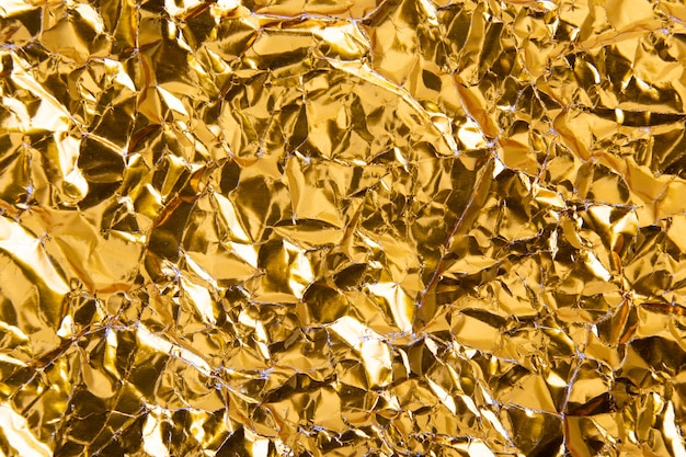 Gold crumpled foil paper texture background.