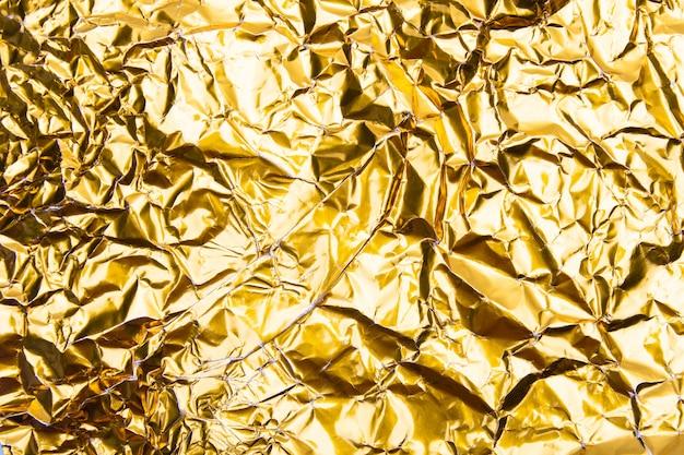 Gold crumpled foil paper texture.