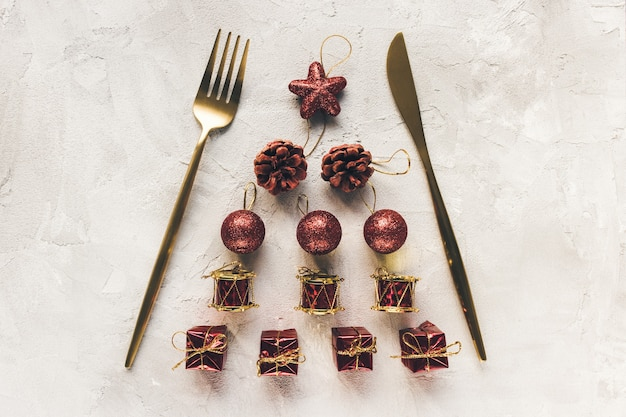 Gold cutlery on a christmas decoration on white surface
