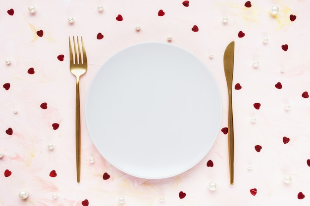 Gold cutlery and plate on pink with hearts. valentines day, meal, dinner and date concept
