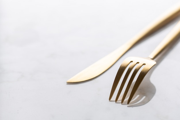 Gold cutlery set on marble