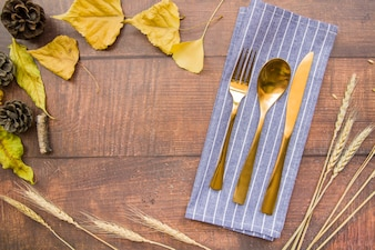 Gold cutlery set on napkin with leaflets