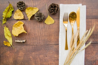 Gold cutlery set on napkin with wheat