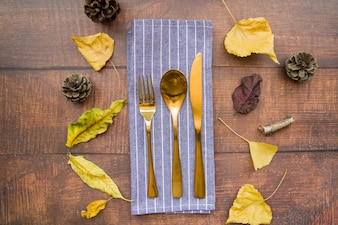 Gold cutlery set on striped napkin with strobiles