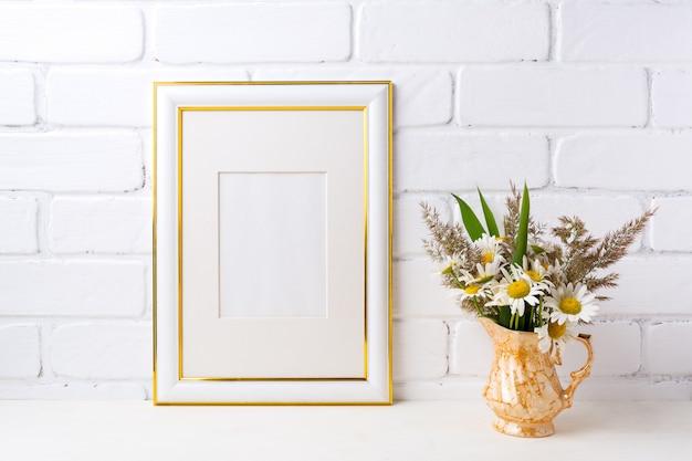 황금 꽃병에 카모마일과 잔디와 골드 장식 프레임