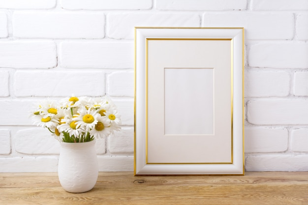 Gold decorated frame  with chamomile bouquet in rustic vase