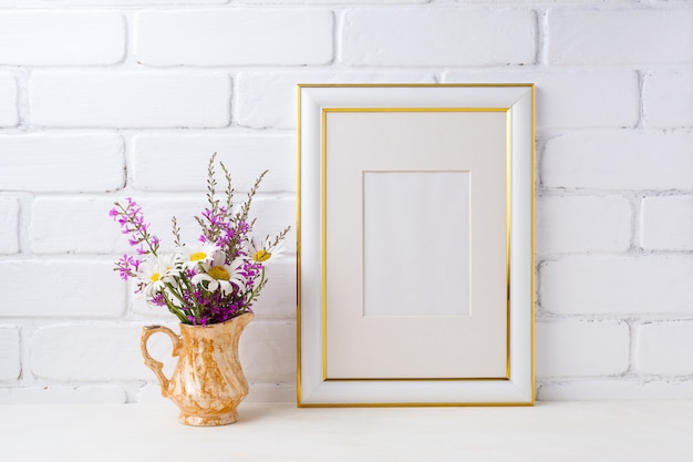 Gold decorated frame  with chamomile and purple flowers in golden pitcher