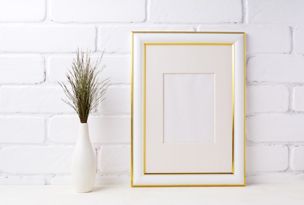 Gold decorated frame  with dark grass in vase near brick wall
