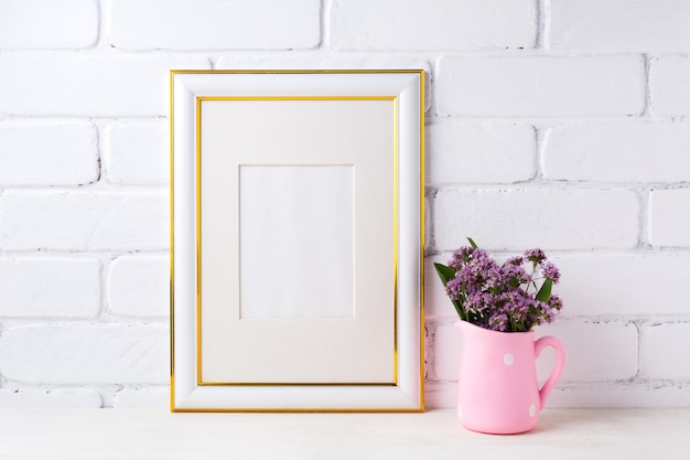 Gold decorated frame  with purple flowers in pink rustic pitcher