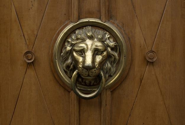 口にリングが付いたライオンの形をした金のドアハンドル。クローズアップショット