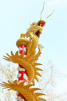 Gold dragon on pole against tree and sky