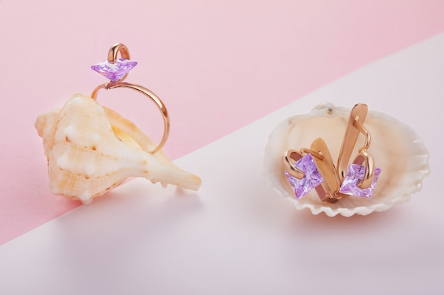Gold earrings and amethyst ring in sea shells