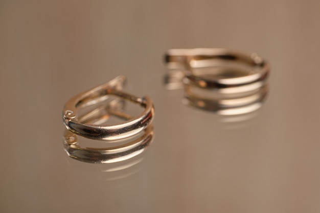 Gold earrings with a simple design on a glass table.