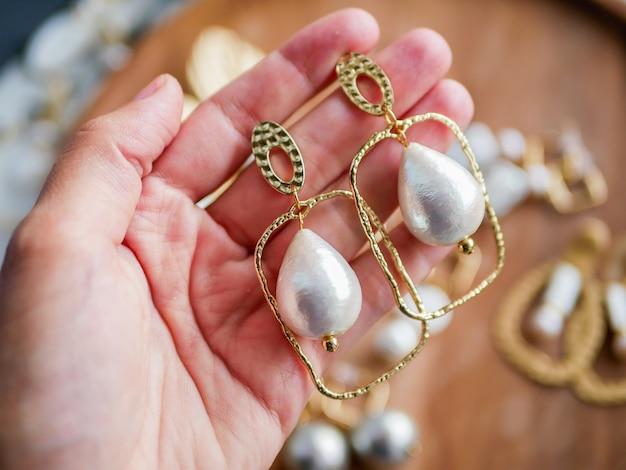 金のイヤリング。女性のジュエリー。ヴィンテージ装飾背景。木製トレイの美しい黄金色のブローチ、ブレスレット、ネックレス、イヤリング。フラット横たわっていた、トップビュー