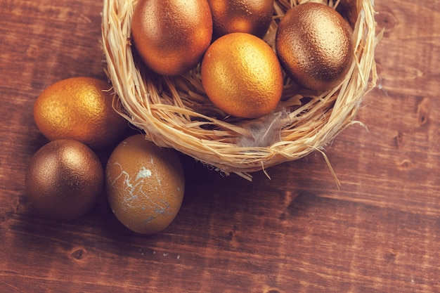 Gold easter eggs on wooden table