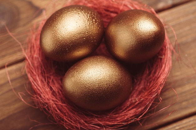 Gold eggs on wooden table