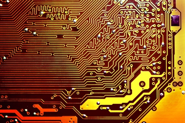 ゴールドの電子マザーボード回路がマクロの背景をクローズアップ