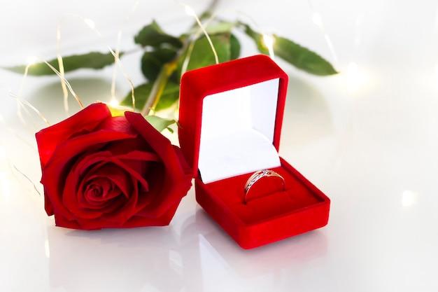 Золотое обручальное кольцо в красной коробке с розой