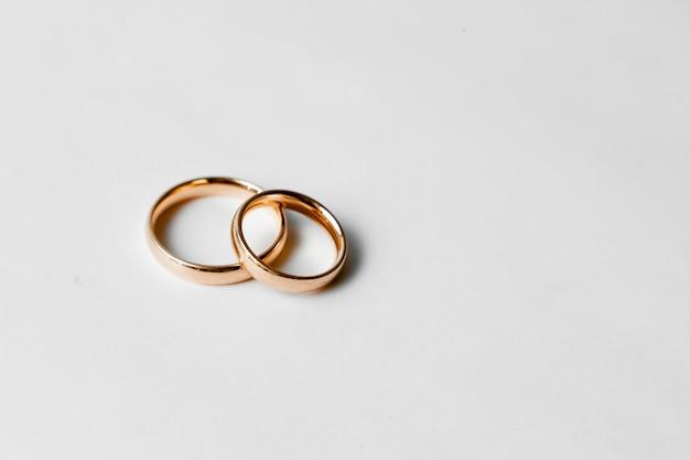 Золотые обручальные кольца на белой стене