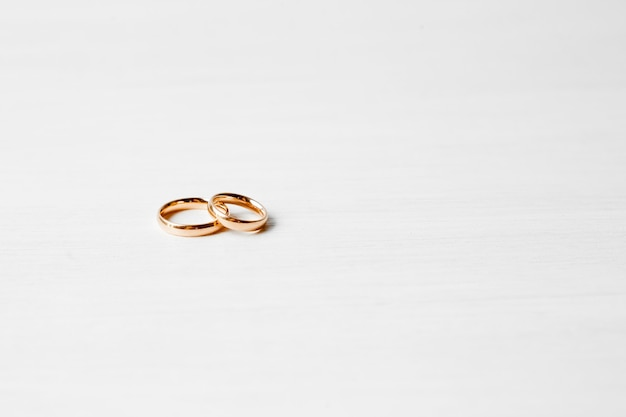 Gold engagement rings on white wall