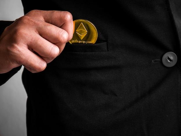 ゴールドイーサリアムコインが黒いスーツに置かれました。