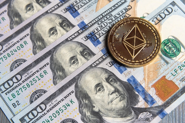 Криптовалюта gold ethereum на доллары сша. крупный план цифровой криптовалюты. обмен, бизнес, торговля. прибыль от майнинга криптовалюты. майнер с долларами и золотой монетой эфириума.