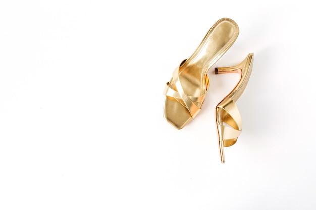 Gold female slippers shoes on white linen