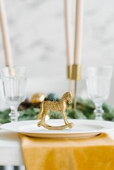 Золотая фигурка старинного коня в оформлении праздничной сервировки рождественского ужина или обеда