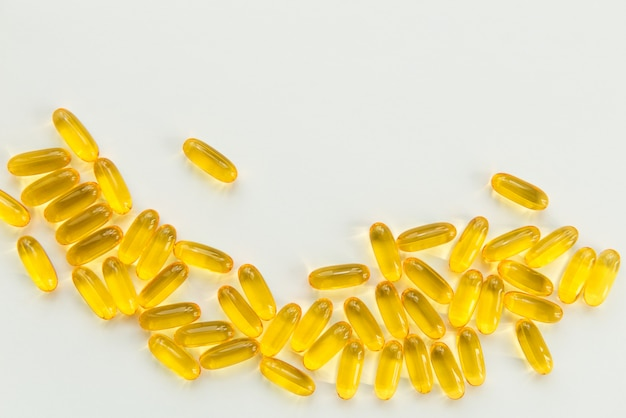 Gold fish oil capsules on white background with copy space. health and pharmacy theme