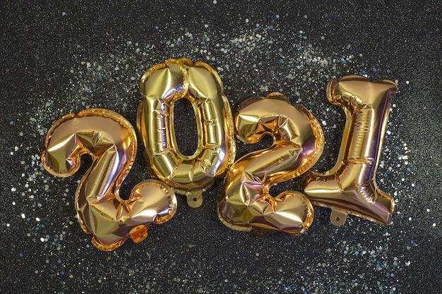 Золотые шары фольги в виде цифр 2021 на черном