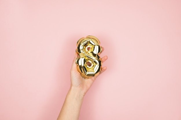 Gold foil balloons numeral 8 in femine hand on pink surface. happy womens day