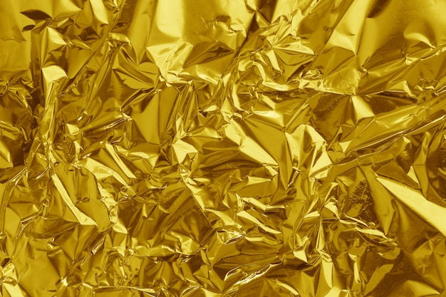 Gold foil leaf shiny texture, abstract yellow wrapping paper and design art work.
