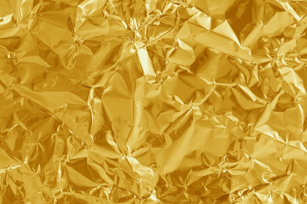 Gold foil leaf shiny texture, yellow wrapping paper for background.