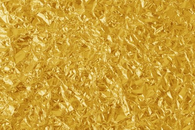 Золотая фольга лист блестящей текстуры, желтая упаковочная бумага для фона.