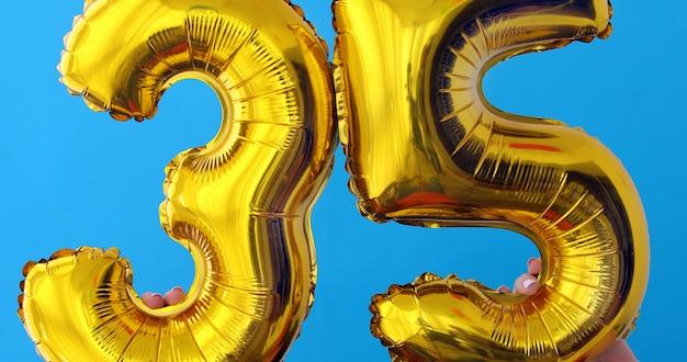 Gold foil number 35 celebration balloon on a blue