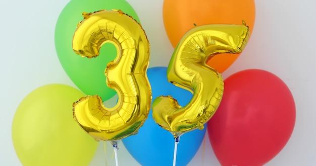 Gold foil number 35 celebration balloon on a color