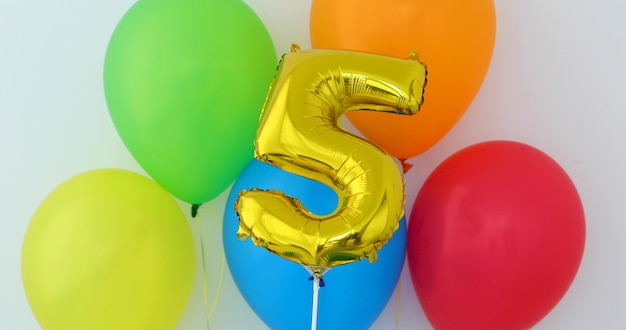 Gold foil number 5 celebration balloon on a color