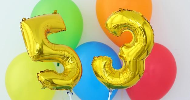 Gold foil number 53 celebration balloon on a color