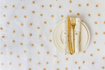 Gold fork and knife on light plate