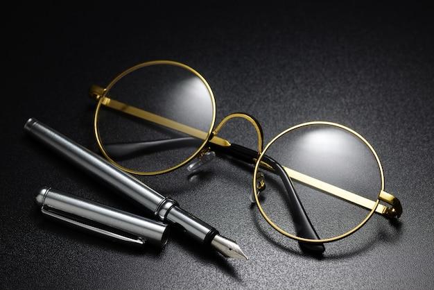 Классические круглые очки в золотой оправе и перьевая ручка