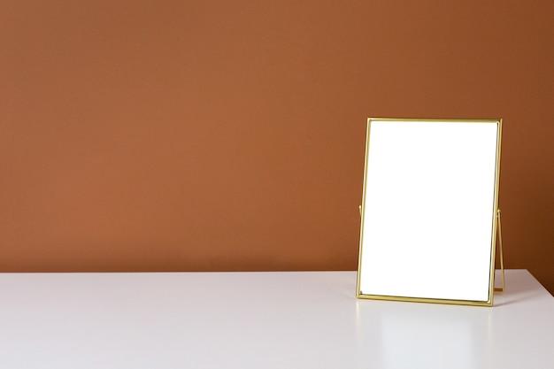 어두운 오렌지 벽 배경으로 흰색 테이블에 골드 프레임 copyspace