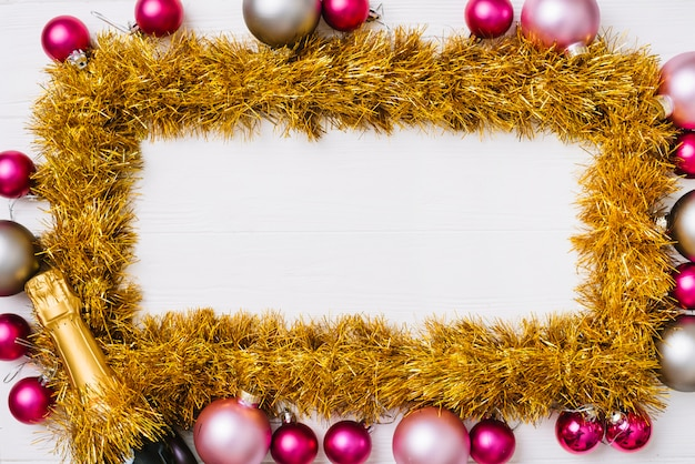 Gold frame from tinsel with baubles