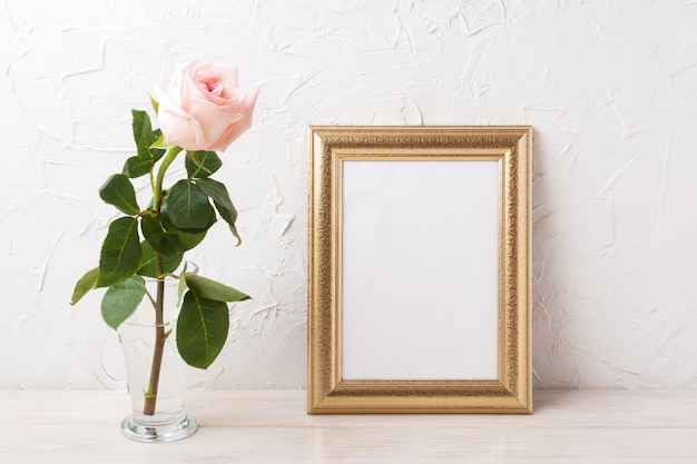 Gold frame mockup with tender pale pink rose in glass