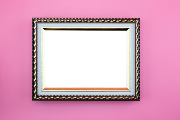 Gold frame photo border or picture with copy space isolated on pink background.