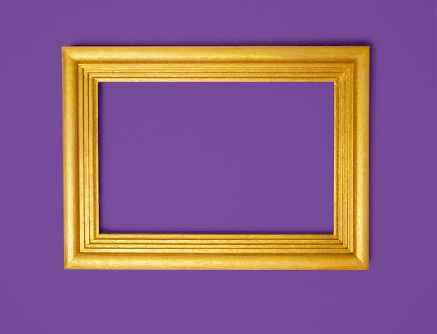 Gold frame on a purple paper background. holiday background, halloween, place for text