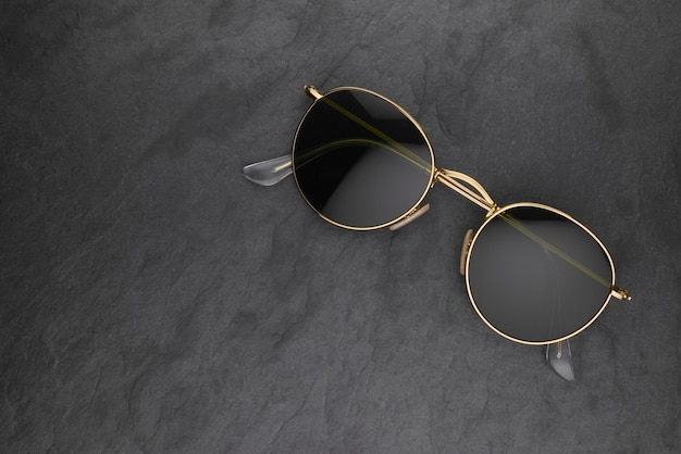 Gold frame round black sunglasses on black slate surface with copy space.