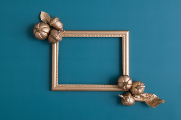 Gold frame with pumpkins, leaves, acorns on a colored background with copy space. creative autumn concept
