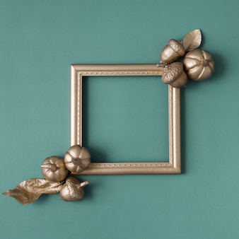 Gold frame with pumpkins, leaves, acorns on a green background with copy space. creative autumn concept