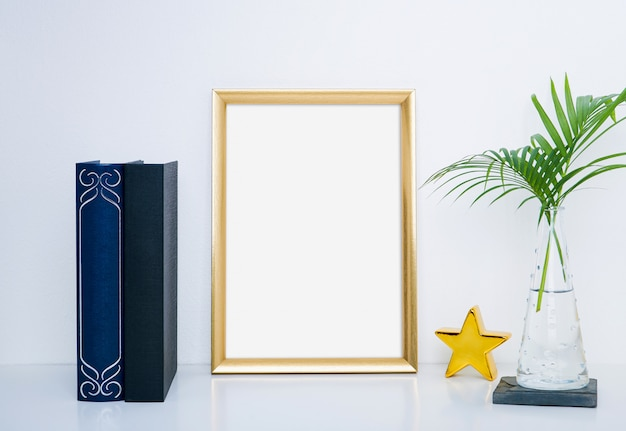 Gold frame with vase and object for interior decoration.