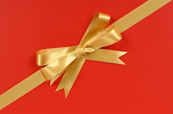 Gold gift bow ribbon corner diagonal isolated on red wrapping paper background